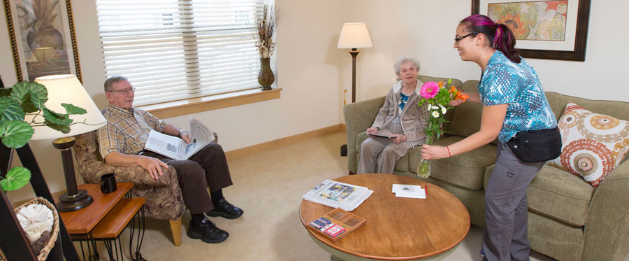 elderly couple in an Attic Angel Apartments living room receiving flowers from a younger female
