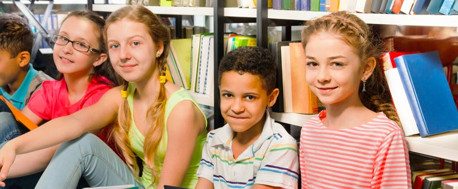 diverse children sitting in front of library books
