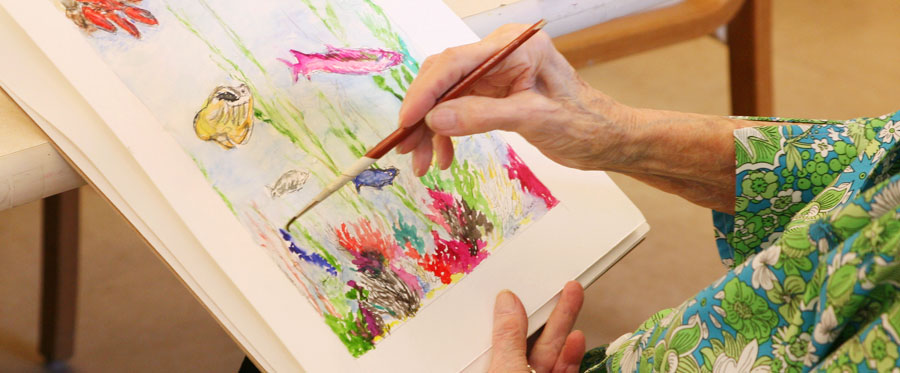 elderly woman's hand painting at Attic Angel Community