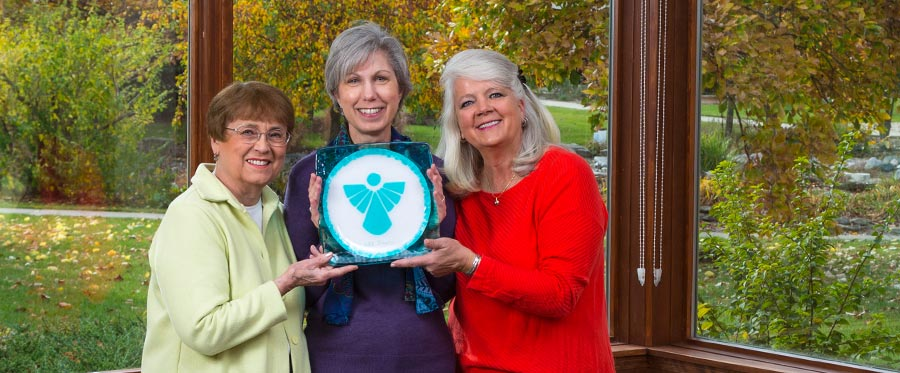 three elderly women holding a blue plate with an angel with a fall colored trees in the background at Attic Angel Community